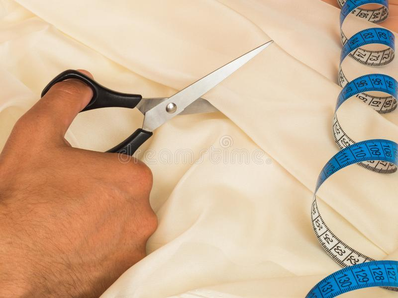 Black scissors in hand cutting out textile. Close-up stock photo