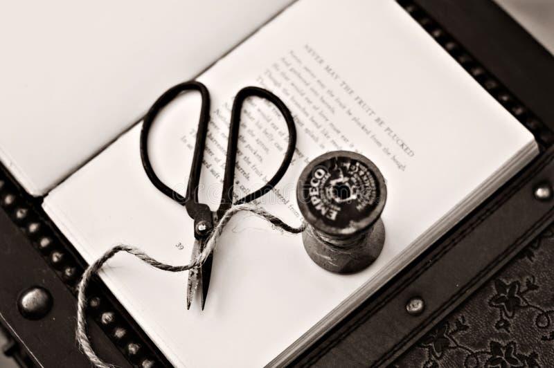 Black Scissors Near Thread Reel on White Book Page stock photos
