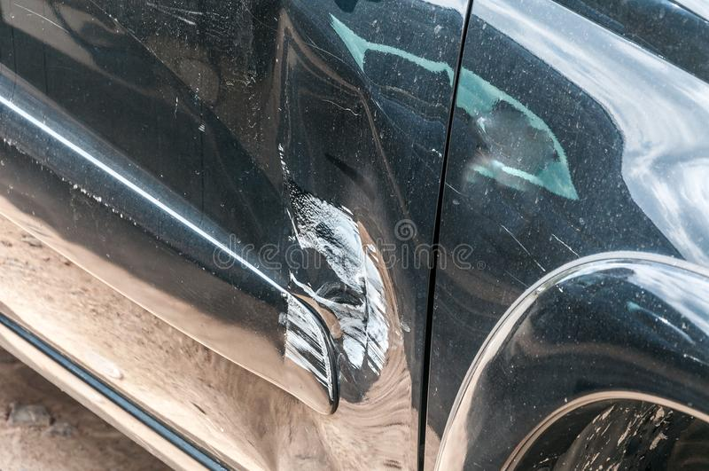 Black scratched car with damaged paint in crash accident on the street or collision on parking lot in the city with dented doors royalty free stock photography