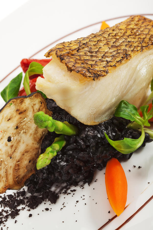 Black Sea Bass. Chile Sea Bass (black sea bass) served with Black Risotto, Herbs and Vegetables stock photography