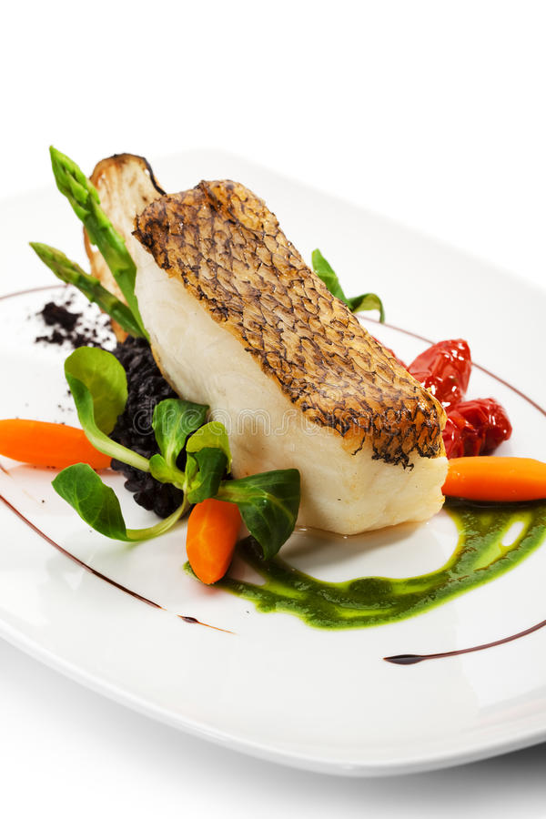 Black Sea Bass. Chile Sea Bass (black sea bass) served with Black Risotto, Herbs and Vegetables stock photo