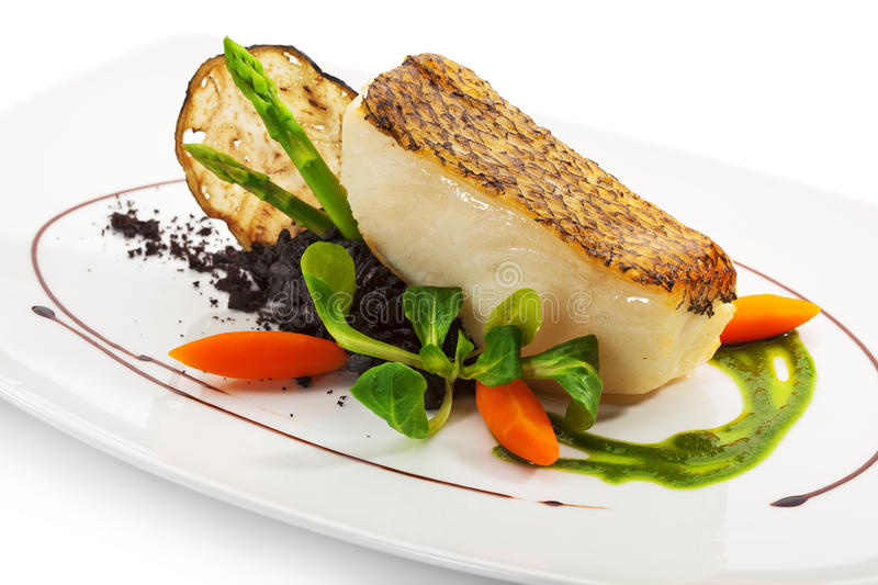 Black Sea Bass. Chile Sea Bass (black sea bass) served with Black Risotto, Herbs and Vegetables royalty free stock image