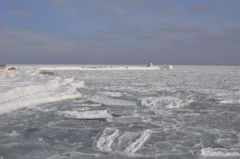 The Black Sea, ice bound in winter, under a cloudy sky. Snowy icy shore and pier stock photography