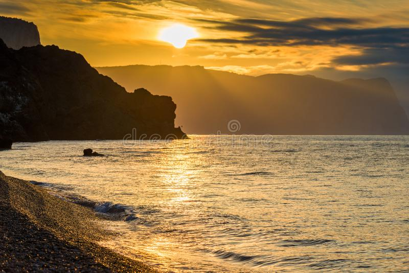 The Black Sea in the rays of the rising sun, a view of the water and rocks. Orange Tone`s Photo royalty free stock image