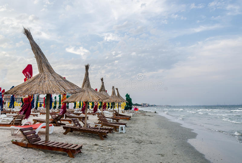 The Black Sea shore, sea side with sand, umbrellas, sun beds and water. Blue sky stock images