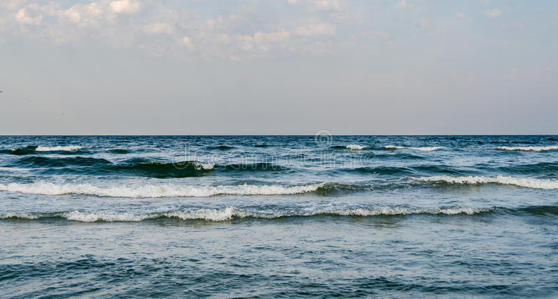 The Black Sea shore, water waves, blue sky. Sea side royalty free stock photo