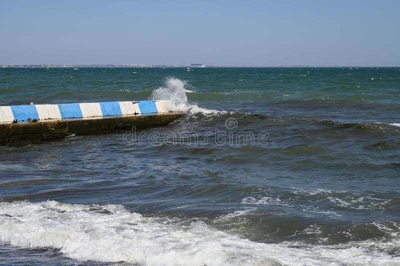 Black sea, Small waves break on the concrete breakwater. Sunny day cloudless sky.  royalty free stock photo