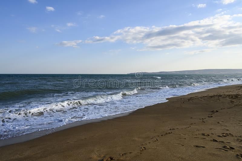 Black sea Sunny autumn day. Sandy beach, small wave and light clouds in the sky stock images