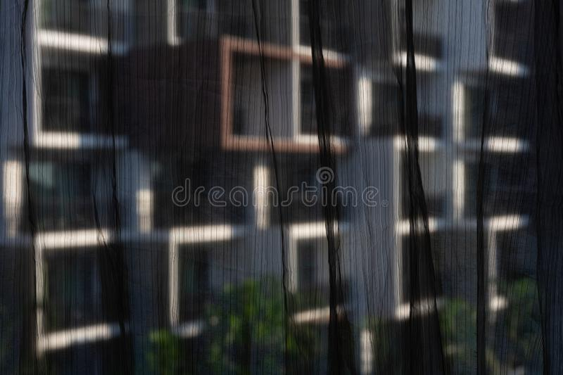 Black see through curtains with blurred building background through window frame. Selective focus on black see through curtains royalty free stock photos