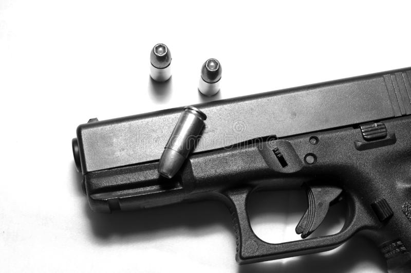 A black semi automatic 9mm pistol on a white background with three hollow point bullets stock images
