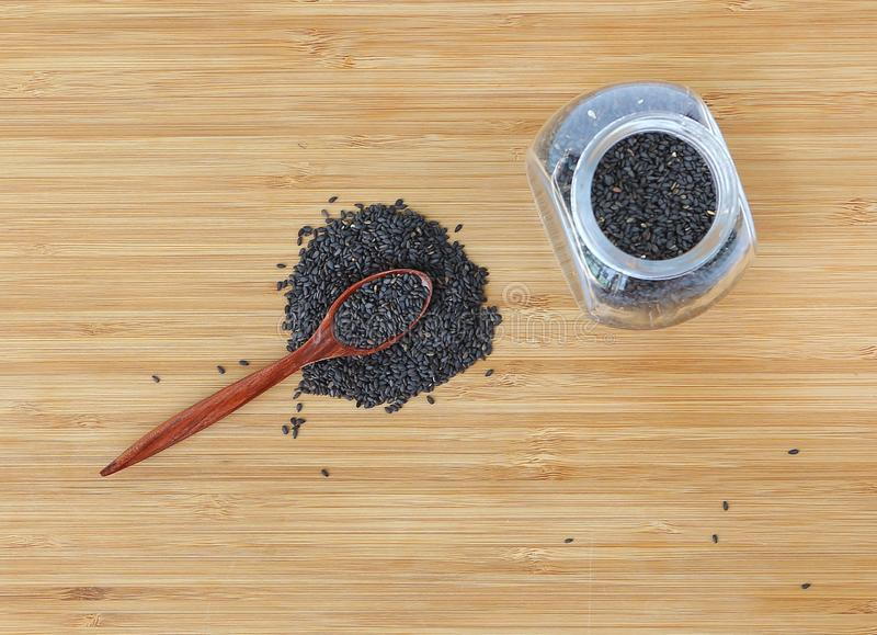 Black sesame in bottle and wooden spoon on bamboo wooden board, Top view stock images