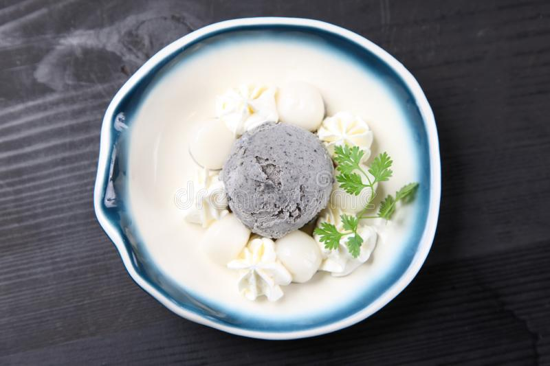 Black sesame seeds icecream with rice-flour dumplings. On a dining table stock images