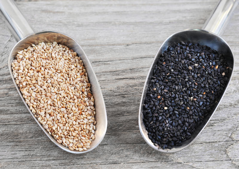 Black Sesame Seeds and White Sesame Seeds. On the wood backgraund royalty free stock photos