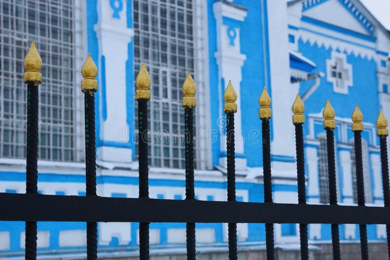 Black sharp iron bars of the fence against a blue white wall with windows. Black sharp metal bars of the fence against a blue white wall with windows royalty free stock photo