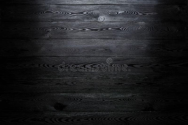Black shiny wooden abstract background with darkening at the edges royalty free stock photo