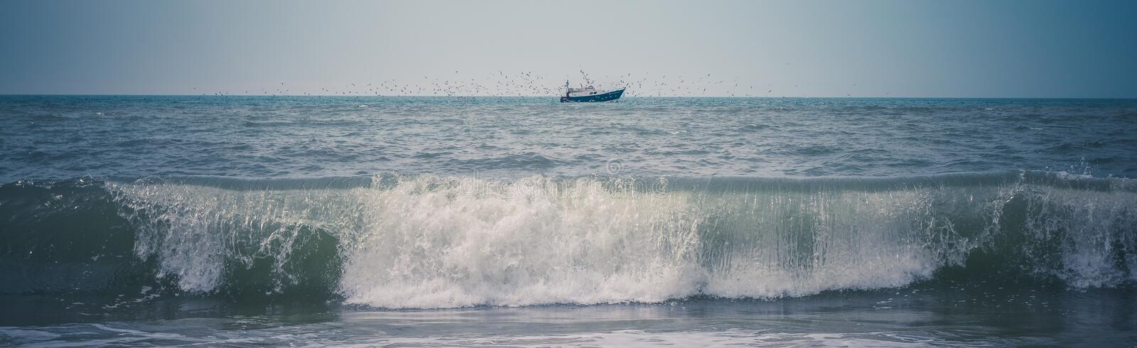 Black Ship on Green Sea Under White and Blue Sky at Daytime stock photography