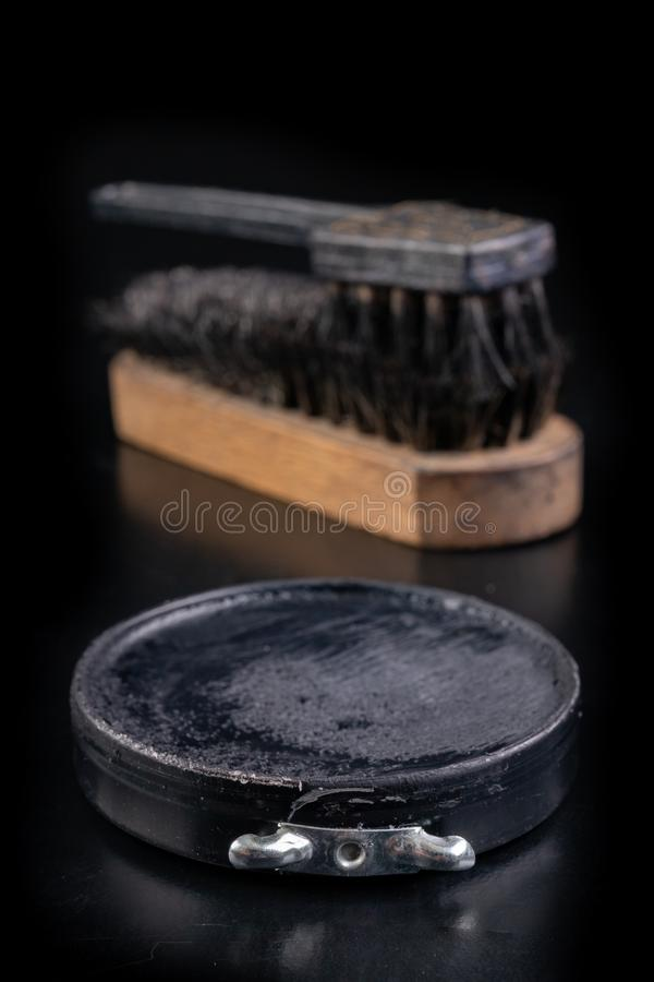 Black shoe polish, brush and shoes on the table. Accessories for cleaning leather footwear royalty free stock images