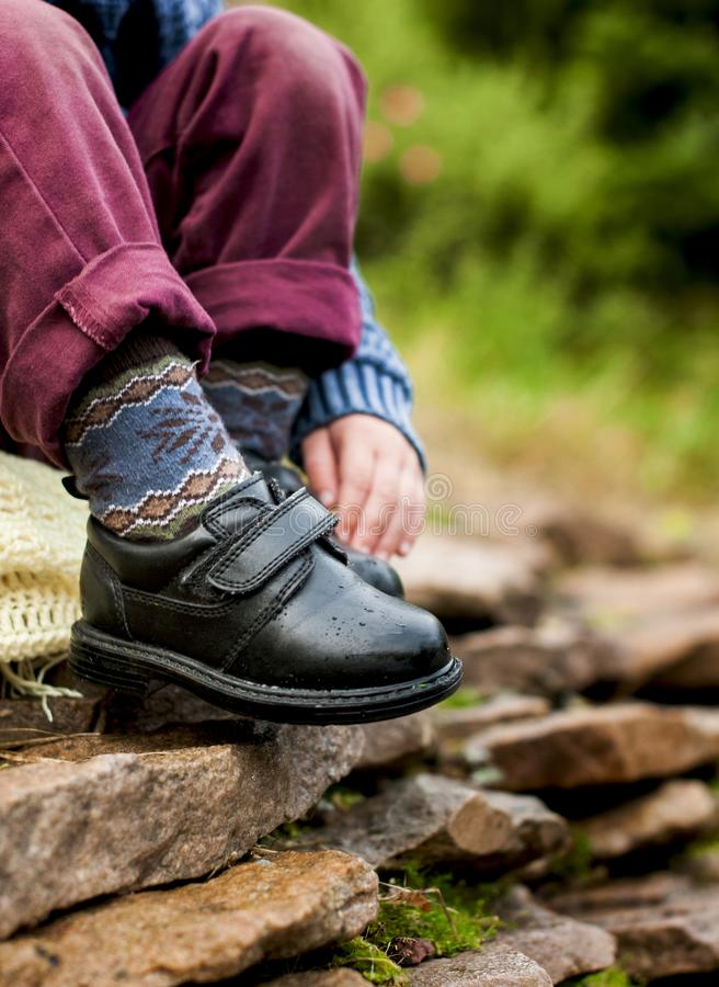 Black shoes with buckles on child legs. With colored socks on stones royalty free stock images