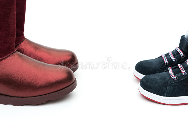 Black shoes for son and red ones for mom as filiation concept. Black shoes for son and red ones for mom on white as filiation concept stock photography