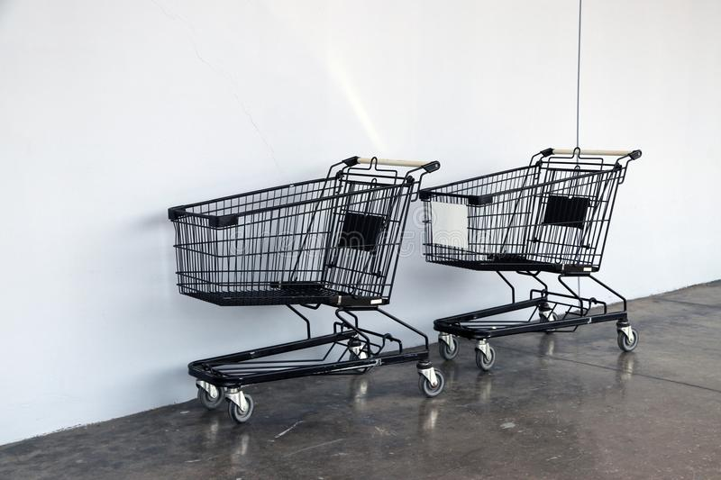 Black shopping Cart on the floor and white background. trolley is a cart supplied by a shop, especially supermarkets. stock photo