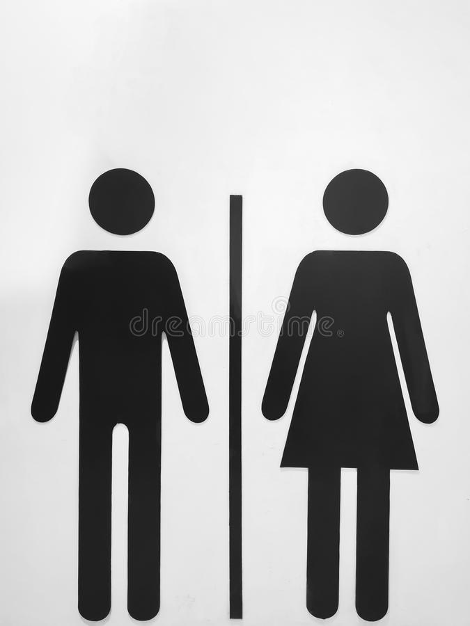 Black sign symbolizing women and men on a white wall. And white background stock images
