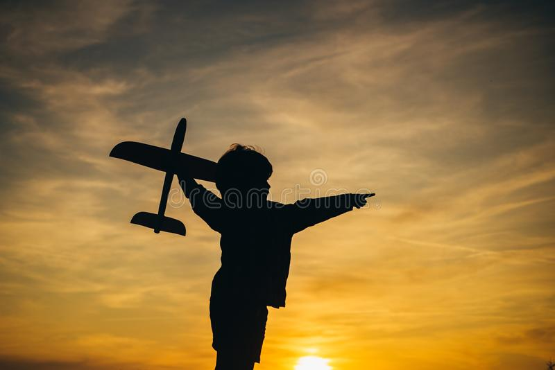 Black silhouette of cute happy child running at countryside and holding toy plane in hand. Happy kid on summer field stock photography