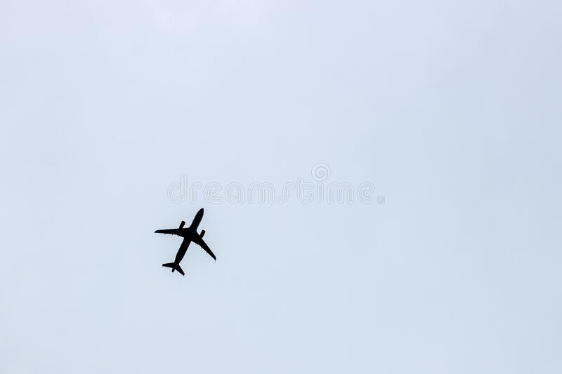 Black silhouette of a flying airplane against a blue gray sky background.  stock photo
