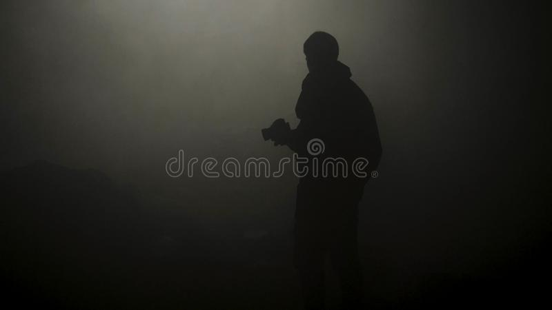 Black silhouette of man standing in smoky dark. Stock footage. Mysterious silhouette of young man stands in darkness lit stock photo