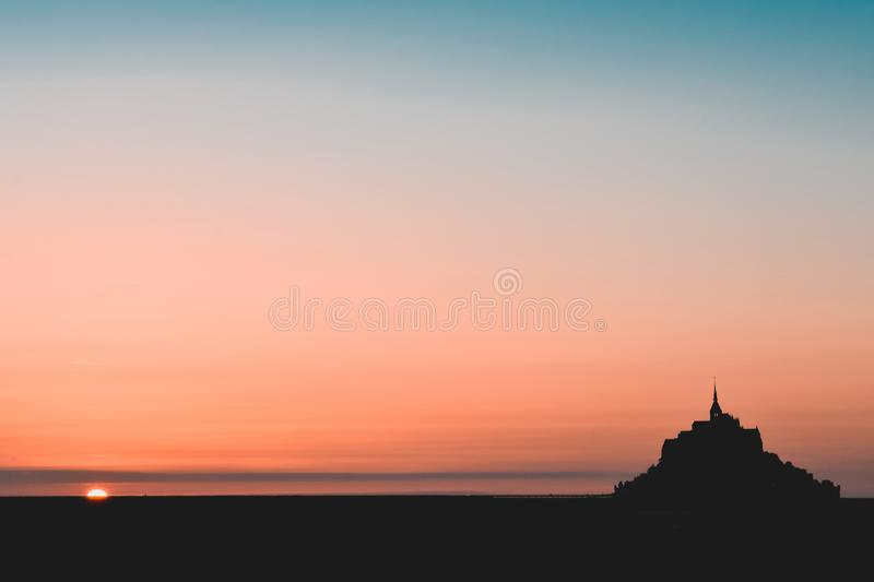 Black silhouette of the Mont Saint Michel in a orange and teal sky.  stock image