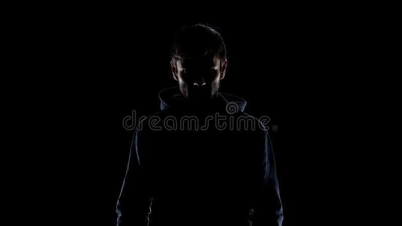 Black silhouette of mysterious man wearing hood, intention to commit crime stock photo