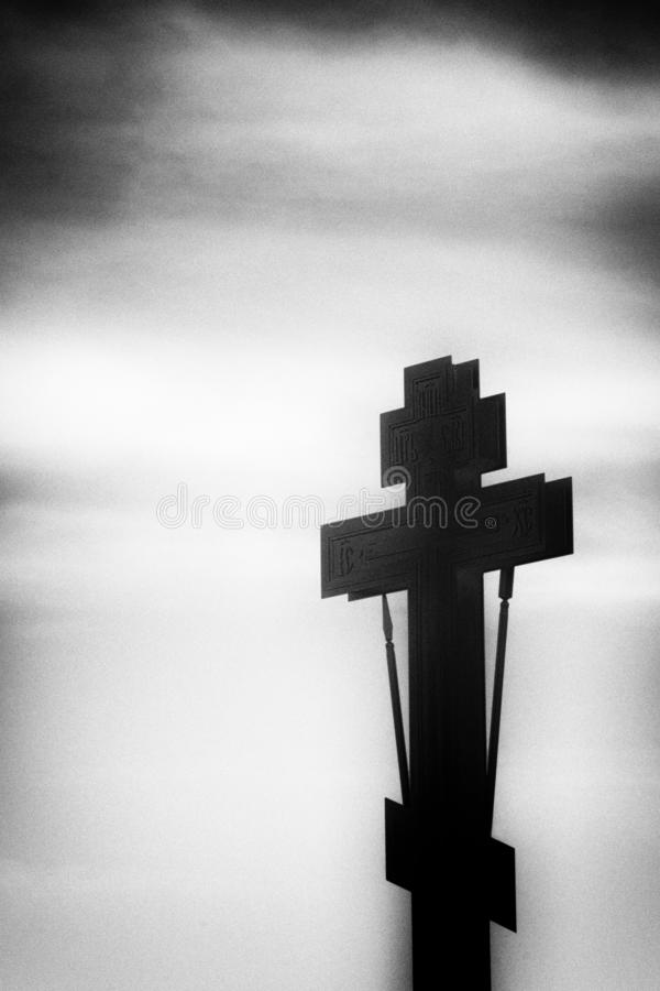 Black silhouette of an Orthodox cross and lantern in a black frame on a white background royalty free stock photography