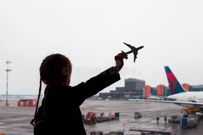 Black silhouette of a small airplane model toy on airport in kids hands stock images