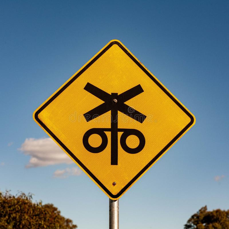 Rail crossing ahead - Australian signs found along the road. Black silhouette of symbols that represent crossing and lights at a railway crossing - Australian royalty free stock photo