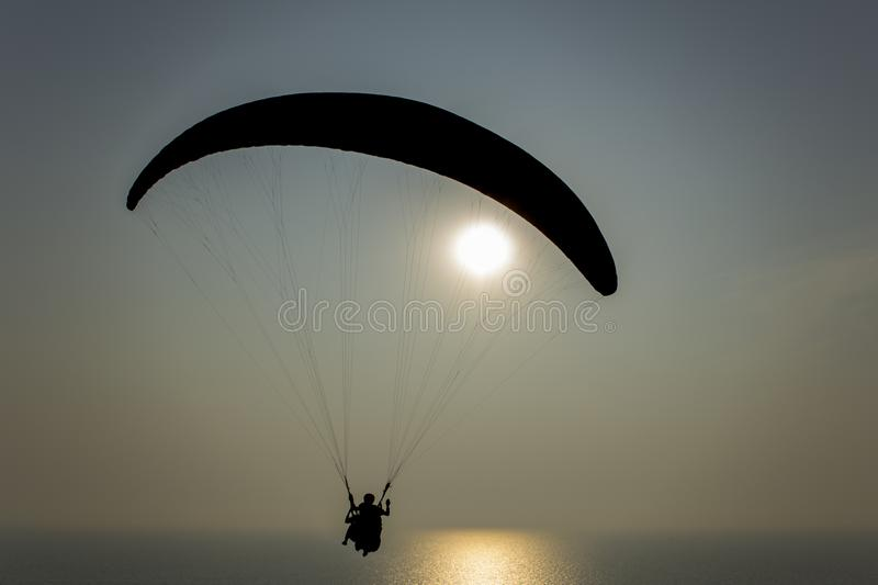 Black silhouette of a tandem of paragliders on a parachute flying over the evening ocean with a sun path during sunset stock photography