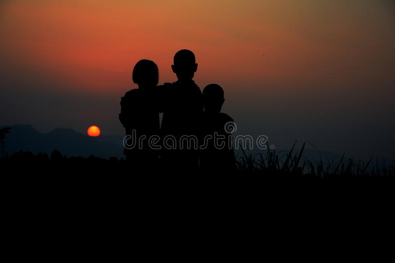Silhouette of three children standing together. There is a sky at sunset royalty free stock photos
