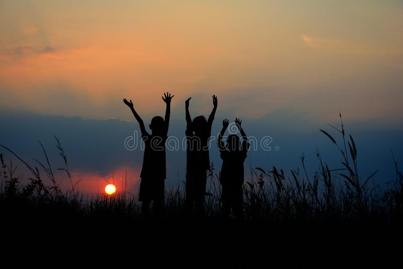 silhouette of three children standing together. There is a sky at sunset stock images