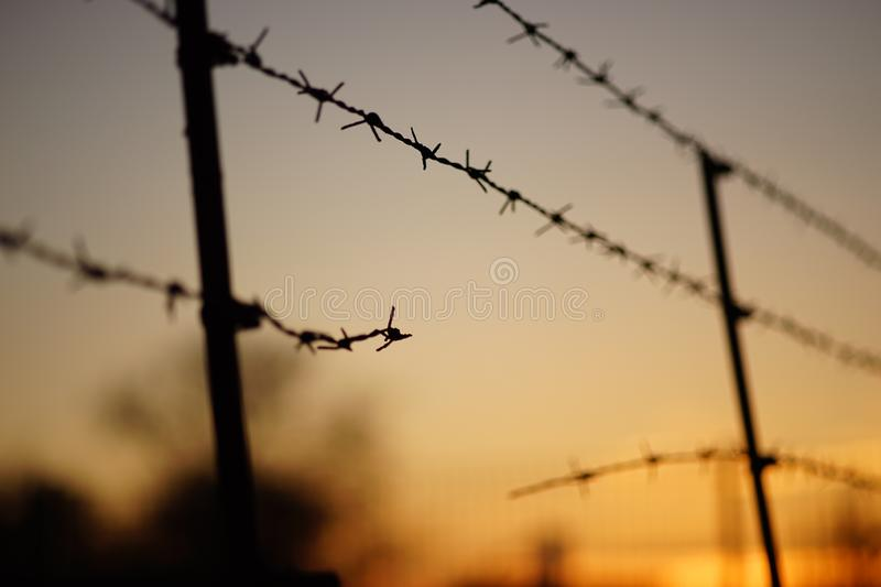Black silhouette of a torn barbed wire fence at sunset.  royalty free stock photography