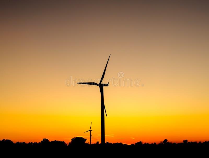 Wind turbine outlines on orange sky. Black silhouette of wind turbines against orange sky at dusk stock photography