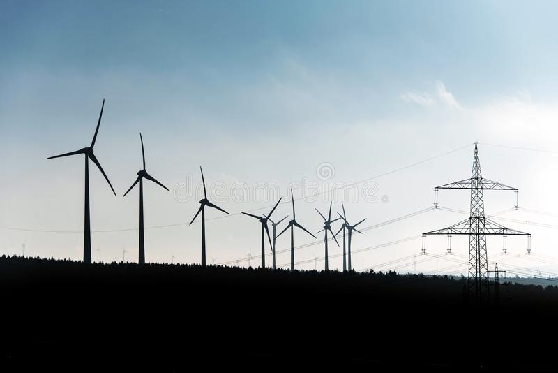 Black Silhouette of windturbines energy generator on blue sky at a wind farm in germany. Black Silhouette of windturbines energy generator on an blue sky at a stock image