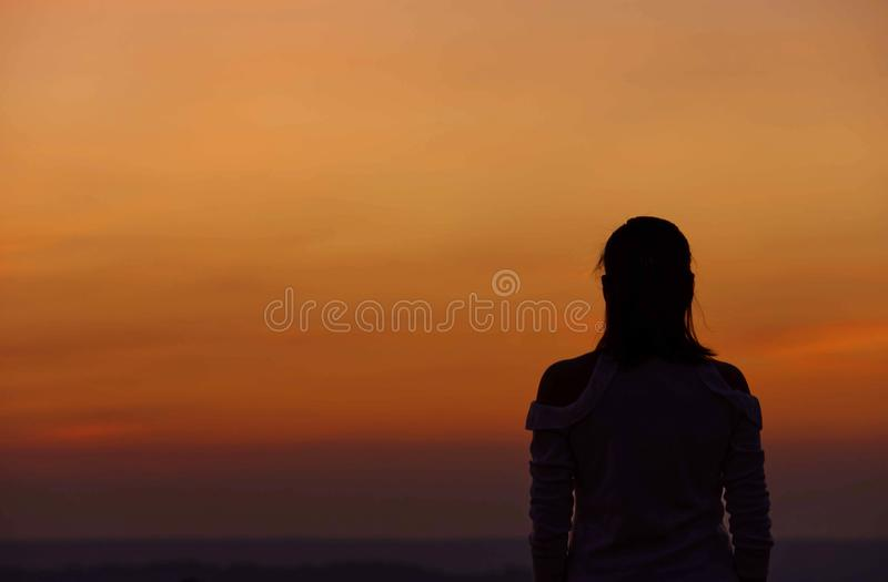 The black silhouette of a woman Background sky orange light of sunset stock image