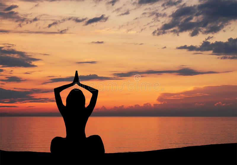 A black silhouette of a woman doing yoga on a sunset. A black silhouette of a sporty woman doing a yoga. The image is taken on an orange sunset background stock image