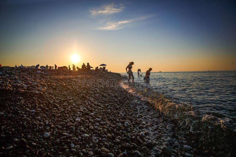 Black silhouettes of people on the beach in the sunset light of the orange sun. Pebble beach Batumi at sunset, tourists on the beach meet the sunset stock photos