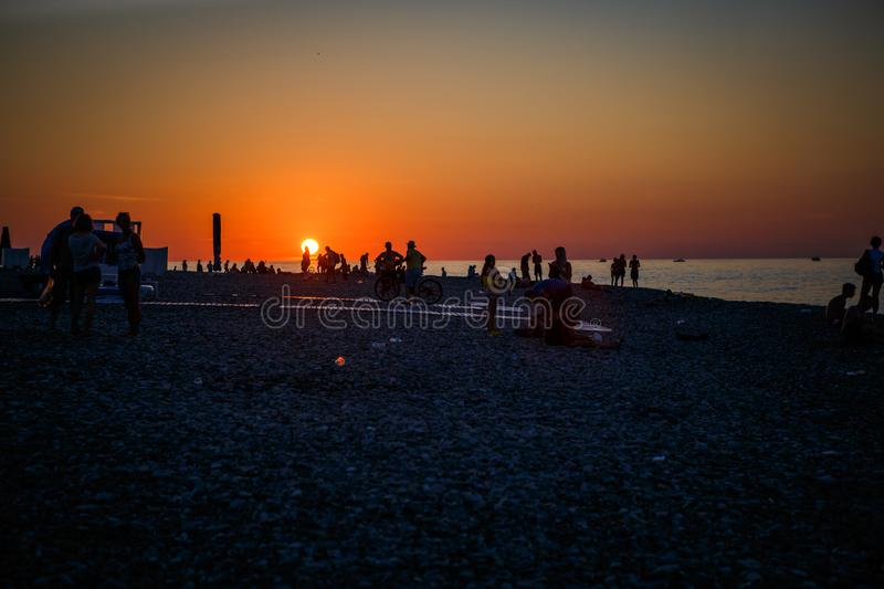 Black silhouettes of people on the beach in the sunset light of the orange sun. Pebble beach Batumi at sunset, tourists on the beach meet the sunset royalty free stock photography