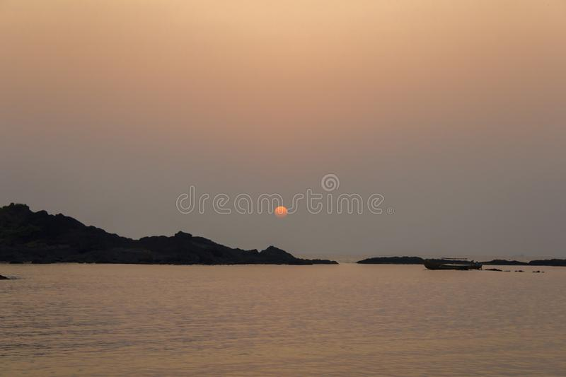 Black silhouettes of rocks and the sun over the ocean in the evening, view from the sea stock image