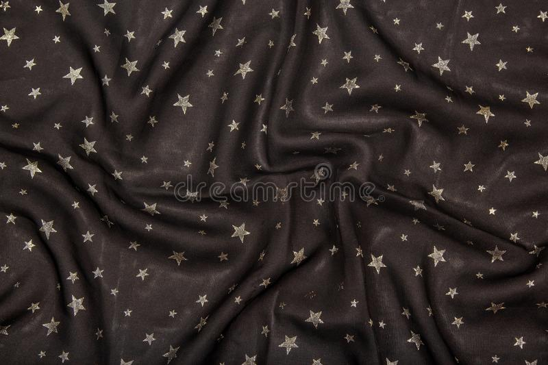 Black silky fabric with glittering metallic stars royalty free stock photography