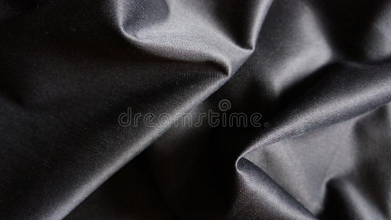 Close-Up Black Silky Cloth Fabric Backdrop with Curves royalty free stock photography