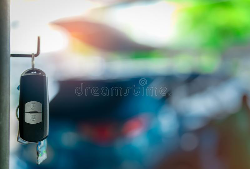 Black and silver car key hang on metal pole on blurred background of luxury blue SUV car. Car rental and automobile insurance. Auto leasing and sale. Used royalty free stock photo