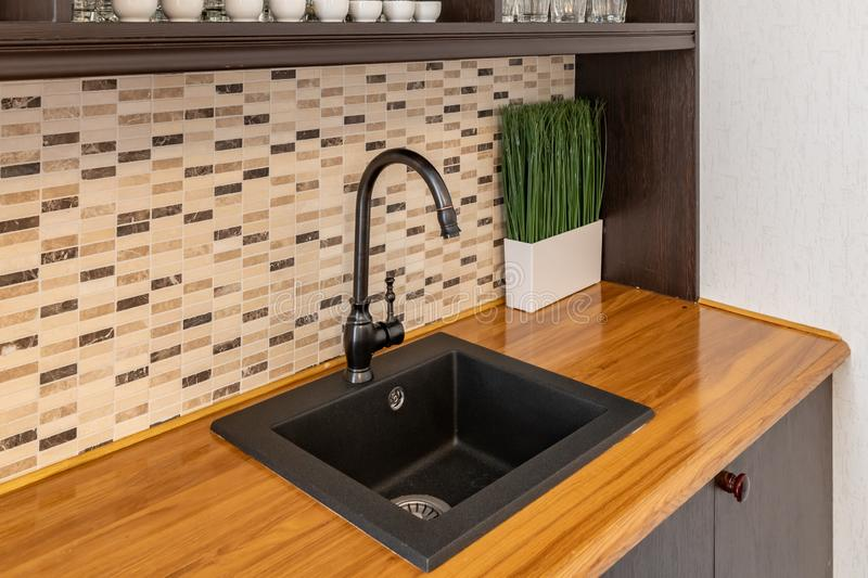 Black sink in the kitchen. Modern kitchen in the attic with black kitchen cabinets stock photos