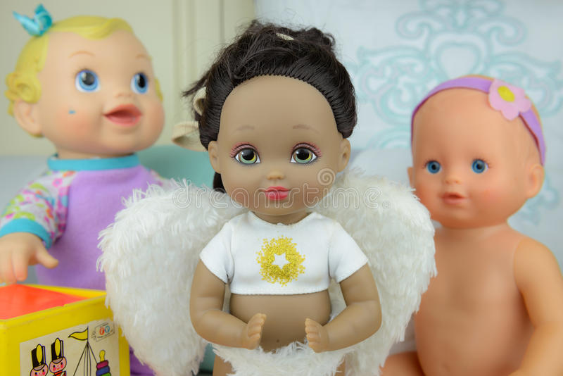 Black skin doll wearing angle suit and wings, girl. Group of dolls, black skin doll in angle suit, white wings, girl royalty free stock images