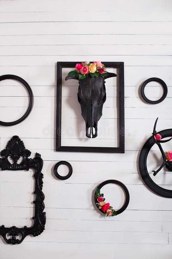 Black skull of a deer and horns on a wooden white wall with empty frames for paintings. The concept of decorating a wooden white w. All in the Gothic style in stock image